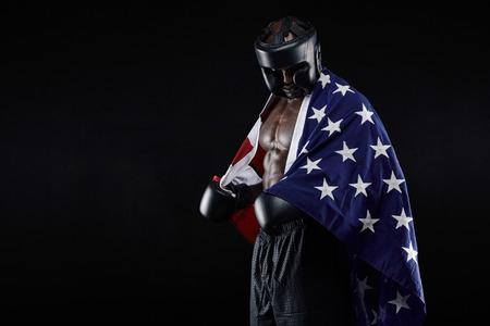 bandera estados unidos: Retrato del boxeador de sexo masculino joven con la bandera americana en el fondo negro. Hombre africano en equipo de boxeo mirando hacia abajo.
