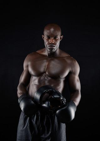 hombres sin camisa: Retrato del boxeador profesional masculino contra el fondo negro. Hombre joven fuerte y musculoso en equipo de boxeo. Foto de archivo