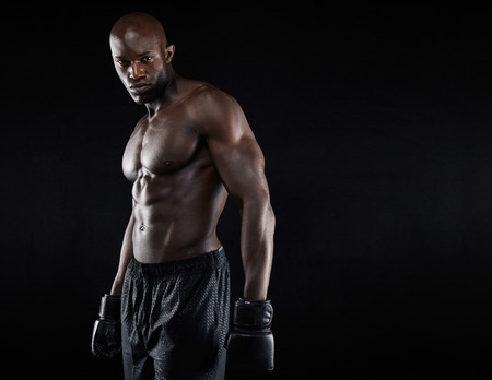 Portrait of muscular male boxer with boxing gloves against black background. Professional boxer looking at camera.