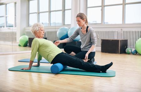 理学療法士のリハビリでアクティブな年配の女性を扱います。歳の女性がジムでパーソナル トレーナーと泡ローラーを使用して運動。