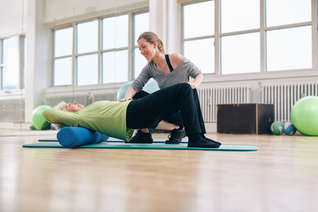 pilates studio: Female trainer instructing senior woman going exercise on a foam roller. Elder woman doing pilates workout with personal instructor at gym. Stock Photo