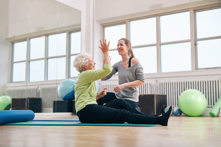 Senior woman giving high five to her personal trainer while sitting on fitness mat at gym. Happy elder woman rejoicing health success with her trainer. Stock Photo - 36042144
