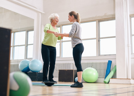 Vrouwelijke trainer helpen senior vrouw in een sportschool te oefenen met een BOSU Balance training platform. Oudere vrouw wordt bijgestaan door sportschool instructeur tijdens training sessie. Stockfoto