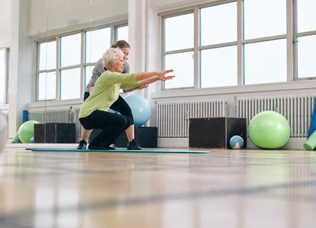 Senior vrouw doen oefening met haar persoonlijke trainer bij gymnastiek. Sportschool instructeur assisteren oudere vrouw in haar workout.