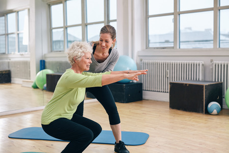 Elderly woman doing exercise with her personal trainer at gym. Gym instructor assisting senior woman in her workout. Stock Photo