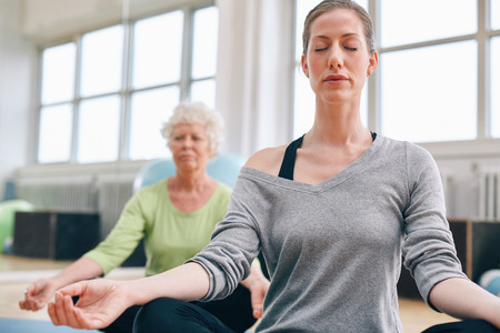 Mature woman doing yoga with senior female in background. Women sitting in lotus pose while mediating in yoga class Stock Photo
