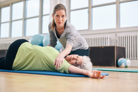 Elderly woman being helped by her personal instructor in the gym for exercising. Female trainer assisting senior woman in her physical training at rehab.