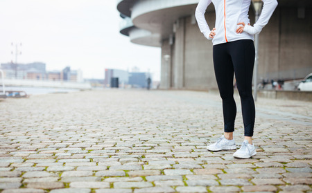 cropped out: Cropped shot of a young woman standing on urban street while out for a run in the city. Fitness female standing with her hands on hips at sidewalk.