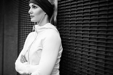 fitness model: Black and white image of young woman wearing earphones standing leaning a wall looking away confidently. Fitness female taking a break for training session. Stock Photo