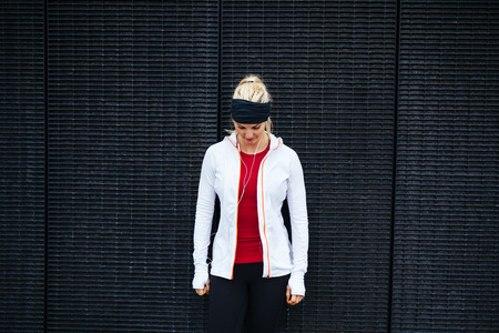 fitness model: Woman standing outdoors in sportswear looking down. Fitness woman standing against a wall. Stock Photo