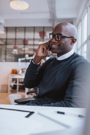 Gelukkig jonge Afrikaanse man zit aan zijn bureau te praten over zijn mobiele telefoon in het kantoor. Afrikaanse uitvoerende behulp van mobiele telefoon tijdens het werk.
