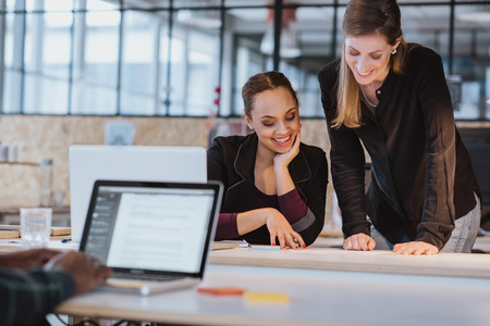 Two young woman at office working on a new creative design. Diverse team of professionals looking at a document smiling. Stock Photo