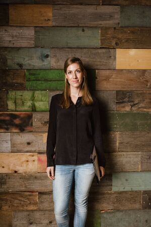 Portrait of attractive young woman standing against a wooden wall. Caucasian woman in casuals in office looking at camera. photo