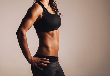 nude abs: Cropped shot of fit womans torso with her hands on hips. Female with perfect abdomen muscles.
