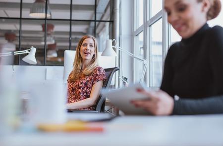 amigas conversando: Mujer joven feliz que tiene una charla amistosa con su compañera de trabajo, mientras que en el trabajo