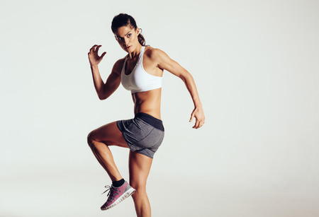 회색 배경에 포즈 꽤 젊은 체육 여자의 스튜디오 샷. 여성 운동 선수 운동과 copyspace에 멀리 찾고.