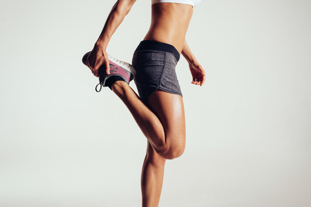 mujeres fitness: Recorta la imagen de una mujer de la aptitud que estira sus piernas contra el fondo gris. Fit corredor haciendo estiramientos mujeres. Foto de archivo