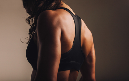 one female: Fit and muscular woman in sports bra standing with her back towards camera. Rear view of fitness female with muscular body.