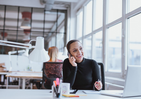modern businesswoman: Young african woman using mobile phone while at work. Female executive in conversation on a mobile phone while sitting at her desk. Stock Photo