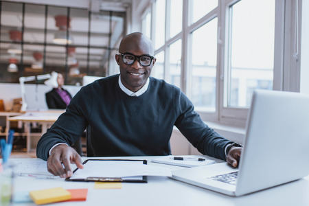 Portrait of confident young man at his desk with laptop doing paperwork. Happy african man looking at camera while at work. Imagens - 36587931