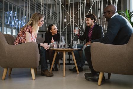 多民族ビジネス チームは新しいビジネスのアイデアを議論するオフィスのロビーに座っています。若い男は、水を飲む。会議中に幸せな若い人々。 写真素材
