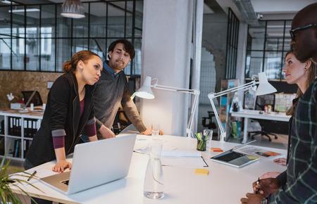 lluvia de ideas: Grupo de m�ltiples personas creativas �tnicos que discuten durante una reuni�n. Equipo de ejecutivos que encuentran alrededor de una mesa Foto de archivo