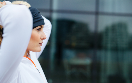 lifestyle woman: Side view of attractive female athlete ready of a run in city. Confident and motivated fitness woman looking away.