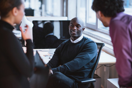 mixed race: Image of young afro american man sitting at desk in office. Young executives at work.