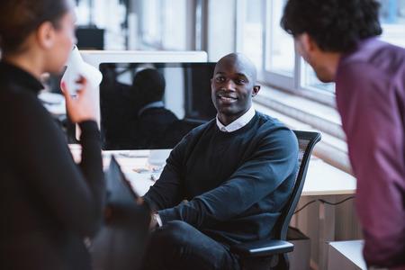 razas de personas: Imagen del hombre afro americano joven sentado en el escritorio en la oficina. J�venes ejecutivos en el trabajo.