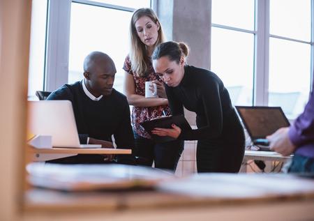 ejecutivo en oficina: Ejecutivo de sexo femenino que muestra la propuesta en el portapapeles para sus colegas. J�venes multirraciales que analizan nuevo plan de negocios en el cargo.