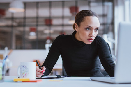 Image of young businesswoman looking at laptop while working at her desk. Female web designer taking notes from internet.