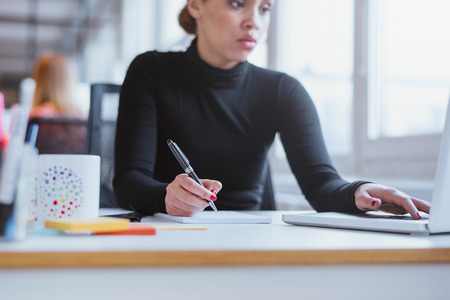 Young woman taking notes from laptop. Female executive working her  desk using laptop and writing notes.