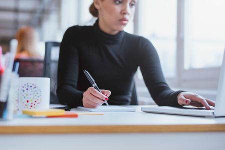 mujer trabajadora: Mujer joven que toma notas de la computadora port�til. Ejecutivo de sexo femenino que trabaja en su escritorio con ordenador port�til y escribir notas. Foto de archivo