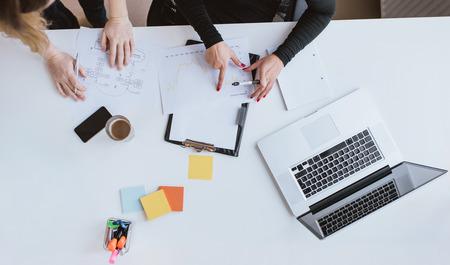 Top Blick auf die Hände der zwei Geschäftsfrau Analyse von Finanzdaten. Kollegen, die auf Diagramm am Schreibtisch im Büro.