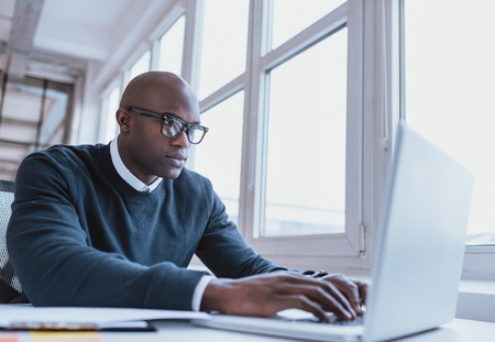forschung: Bild von African American Geschäftsmann arbeitet an seinem Laptop. Gut aussehender junger Mann an seinem Schreibtisch.