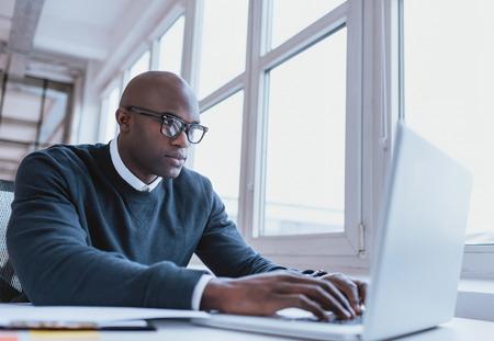 trabajo en la oficina: Imagen de hombre de negocios estadounidense que trabaja en su computadora port�til. Apuesto joven en su escritorio. Foto de archivo