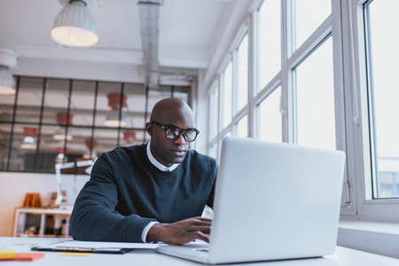 businessman working at his computer: Shot of a bald african businessman working on laptop computer in office. Young web designer sitting at his desk working.
