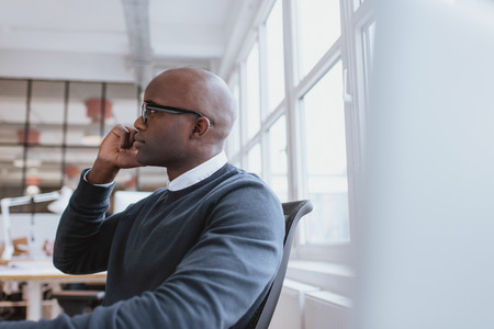 answering call: Side view of african executive sitting at his desk using mobile phone. Young man at work answering a phone call. Stock Photo