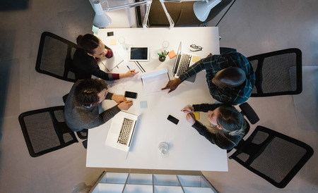 work team: Overhead view of diverse team analyzing data while sitting at office. Multiracial business people in a meeting working on new project. Stock Photo