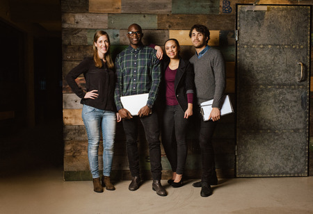organized group: Portrait of successful business team standing together against wooden wall. Full length image of a group of diverse colleagues standing in an office