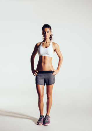 full body woman: Young woman with beautiful slim healthy body posing in studio. Fitness female model in sportswear on grey background Stock Photo