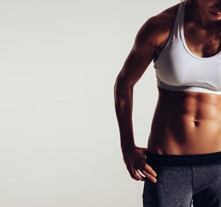 modelos desnudas: Primer plano de una mujer con cuerpo musculoso. Recorta la imagen de la mujer joven del ajuste en ropa deportiva en el fondo gris con copyspace.