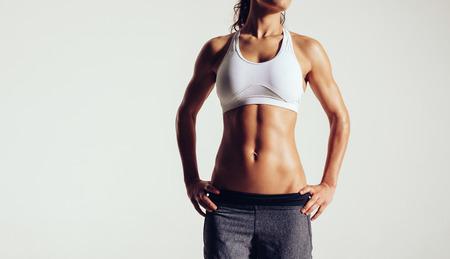 灰色の背景に対してスポーツウェアでポーズ筋肉若い女性の画像をトリミングしました。スタジオで完璧な胴体の女性モデルをフィットします。