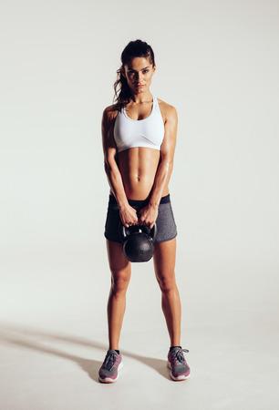 pesas: Fitness mujer haciendo ejercicio con crossfit campana hervidor de agua. Instructor de fitness hermoso sobre fondo gris. Modelo femenino con ajuste muscular y cuerpo delgado.