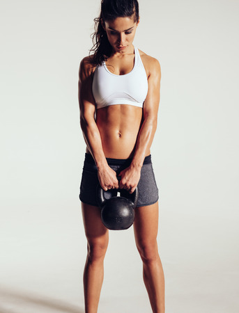 bells: Fitness woman doing crossfit exercise. Tough fitness female model with kettle bell on grey background.