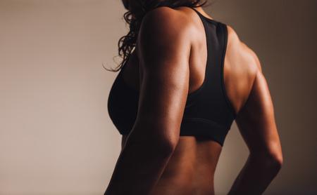 personas de espalda: Detr�s de una mujer atleta en forma y muscular en sujetador deportivo. Vista posterior de la mujer de la aptitud con cuerpo musculoso. Destacado en la espalda.