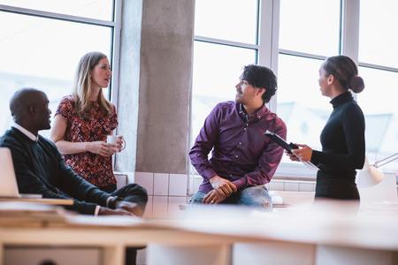 Team jonge professionals met toevallige discussie in kantoor. Executives met vriendelijke discussie tijdens de pauze. Stockfoto