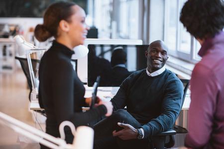 personas hablando: Hombre africano feliz que se sienta en el escritorio con los compañeros de trabajo sonriendo. Ejecutivos de negocios jóvenes durante las vacaciones. Foto de archivo