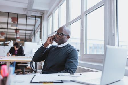 trabajo en la oficina: Hombre joven hablando por su tel�fono m�vil en la oficina. Ejecutivo africano sentado en su escritorio con ordenador port�til Foto de archivo