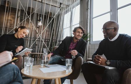 personas reunidas: Ejecutivos j�venes relajados que tienen una reuni�n en el interior. Grupo multirracial de la gente sentada en el vest�bulo de oficina discutiendo el negocio.